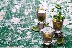 Transparent drink in a glass. With chia seeds, lemon and mint on a wooden background. Selective focus Stock Images