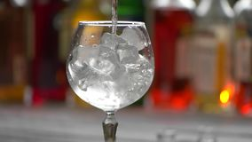 Transparent drink slowly pouring. Wineglass filled with ice. Chill and relax. Ingredient for tom collins stock footage