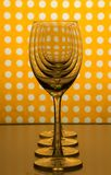 Transparent empty wine glasses one behind the other and yellow orange background with white spots. Four empty transparent wine glasses standing in line one royalty free stock image