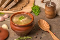 Transparent fish soup with sturgeon, potatoes in clay pot, decor Royalty Free Stock Photos