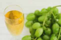 Transparent and fragile glass full of wine near bunch of fresh ripe green grapes on old wooden white planks. Transparent and fragile glass full of wine near royalty free stock photography