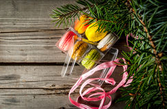 Transparent gift box with cakes macarons s a gift for Christmas. Transparent gift box with cakes macarons on wooden table, under the branches of a Christmas tree royalty free stock images