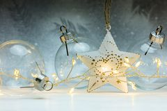 Transparent glass balls with star and glowing garland lights. On decorative silver background royalty free stock image
