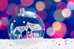 Transparent glass baubles. Transparent Christmas bauble on blue background with snow Royalty Free Stock Photo