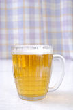 The transparent glass of beer costs on a table. The full glass of beer costs on a table. Close up Stock Photos