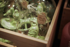 Transparent Glass christmas toys with green birds inside in wooden box Royalty Free Stock Photography