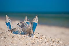 Transparent glass crystals on the sand on a background of blue sea and blue sky Royalty Free Stock Image