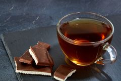 Glass cup of black tea with chocolate pieces on a dark greyish marble background. Top view. A transparent glass cup of black tea with chocolate pieces on a dark Stock Image
