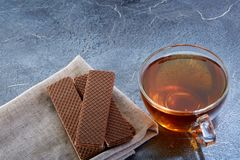 A glass cup of black tea with cookies on a dark greyish marble background. Breakfast background. A transparent glass cup of black tea with cookies on a dark Royalty Free Stock Images