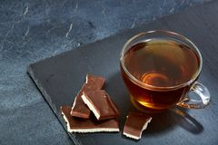 A glass cup of black tea with cookies on a dark greyish marble background. Breakfast background. A transparent glass cup of black tea with cookies on a dark Stock Images