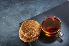 A glass cup of black tea with cookies on a dark greyish marble background. Breakfast background. Top view. A transparent glass cup of black tea with cookies on a Stock Photos