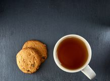 A glass cup of black tea with cookies on a dark greyish marble background. Breakfast background. A transparent glass cup of black tea with cookies on a dark Stock Photo