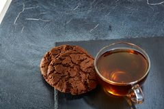 A glass cup of black tea with cookies on a dark greyish marble background. Breakfast background. A transparent glass cup of black tea with cookies on a dark Royalty Free Stock Photos