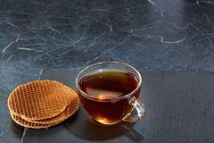 A glass cup of black tea with waffles on a dark greyish marble background. Breakfast background. A transparent glass cup of black tea with waffles on a dark Stock Photo