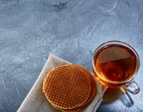 A glass cup of black tea with waffles on a dark greyish marble background. Breakfast background. A transparent glass cup of black tea with waffles on a dark Royalty Free Stock Photo