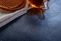 A glass cup of black tea with waffles on a dark greyish marble background. Breakfast background. A transparent glass cup of black tea with waffles on a dark Stock Images