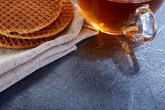 A glass cup of black tea with waffles on a dark greyish marble background. Breakfast background. A transparent glass cup of black tea with waffles on a dark Royalty Free Stock Images