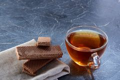 A glass cup of black tea with waffles on a dark greyish marble background. Breakfast background. A transparent glass cup of black tea with waffles on the light Stock Photo