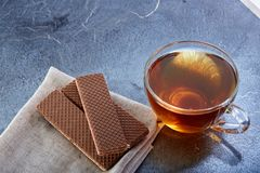 A glass cup of black tea with waffles on a dark greyish marble background. Breakfast background. A transparent glass cup of black tea with waffles on the light Stock Images