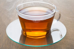 Transparent glass cup of black tea on wooden background, closeup Royalty Free Stock Photography