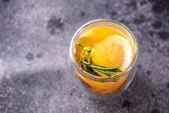 Transparent glass cup with bright yellow tea, on a gray background. Close up, copy space, top view