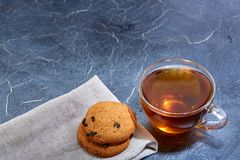 A glass cup of black tea with cookies on a dark greyish marble background, shallow depth of field. Breakfast background. A transparent glass cup of delicious Stock Photography