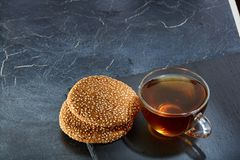 A glass cup of black tea with cookies on a dark greyish marble background, shallow depth of field. Breakfast background. A transparent glass cup of delicious Stock Images