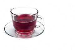 Transparent glass cup with Hibiscus tea on a saucer isolated. On a white background stock photography