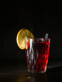 Transparent glass cup with hot hibiscus tea. The vapor from the top. Black background. Royalty Free Stock Photo