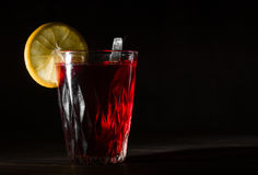 Transparent glass cup with hot hibiscus tea. The vapor from the top. Black background. Royalty Free Stock Photography