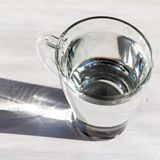 Transparent glass cup of pure cold drinking water on white woode. N table. Copy space Royalty Free Stock Photo