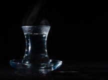 Transparent glass cup with swell the boiling water into it. The vapor from the top. Black background. Stock Image