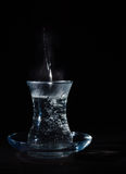 Transparent glass cup with swell the boiling water into it. The vapor from the top. Black background. Stock Photos