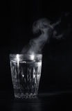 Transparent glass cup with swell the boiling water into it. The vapor from the top. Black background. Space for text royalty free stock photos