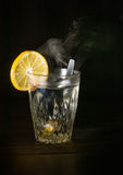 Transparent glass cup with swell the boiling water into it. The vapor from the top. Black background. Royalty Free Stock Photography