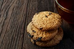Cup of tea with a couple of chocolate chips cookies on a wooden background, top view, selective focus. A transparent glass cup of tea with a couple of tasty Royalty Free Stock Photo