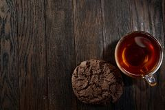 Cup of tea with a couple of chocolate cookies on a wooden background, top view, selective focus. A transparent glass cup of tea with a couple of tasty chocolate Royalty Free Stock Photos