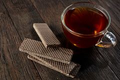 Cup of tea with a couple of chocolate waffles on a wooden background, top view, selective focus. A transparent glass cup of tea with a couple of tasty chocolate Royalty Free Stock Images