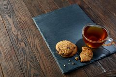 Cup of tea with a couple of cookies on black board over a wooden background, top view, selective focus. A transparent glass cup of tea with a couple of tasty Royalty Free Stock Photos