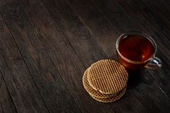 Cup of tea with a couple of waffles on a wooden background, top view, selective focus. A transparent glass cup of tea with a couple of tasty waffles on a a dark Stock Photo