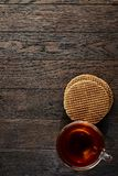 Cup of tea with a couple of waffles on a wooden background, top view, selective focus. A transparent glass cup of tea with a couple of tasty waffles on a a dark Royalty Free Stock Image