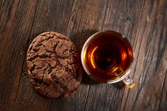 Cup of tea with cookies on a cutting board on a wooden background, top view. A transparent glass cup of tea with delicious chocolate chips cookies on a rough Stock Image