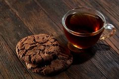 Cup of tea with cookies on a cutting board on a wooden background, top view. A transparent glass cup of tea with delicious chocolate chips cookies on a rough Stock Photos