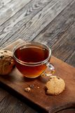 Cup of tea with cookies on a cutting board on a wooden background, top view. A transparent glass cup of tea with delicious chocolate chips cookies on a rough Royalty Free Stock Images
