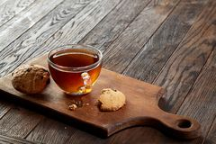Cup of tea with cookies on a cutting board on a wooden background, top view. A transparent glass cup of tea with delicious chocolate chips cookies on a rough Royalty Free Stock Photography