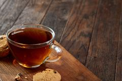 Cup of tea with cookies on a cutting board on a wooden background, top view. A transparent glass cup of tea with delicious chocolate chips cookies on a rough Royalty Free Stock Image