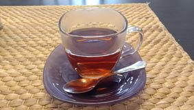 Transparent glass cup with tea on the table and in the hand. royalty free stock photography