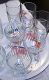 Transparent glass dishes and jars on shelves. Transparent glass dishes, glasses and cans on the shelves are rows Royalty Free Stock Images