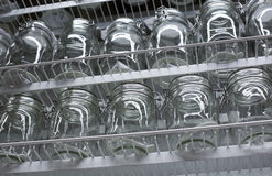 Transparent glass dishes and jars on shelves. Transparent glass dishes, glasses and cans on the shelves are rows Stock Photography