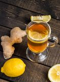 A cup of ginger tea with lemon on a wooden background. A transparent glass filled with ginger tea with lemon. On a blue wooden table. Yellow lemon Royalty Free Stock Photos